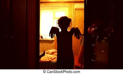 teen girl in a zombie is orange silhouette stretched hands -...