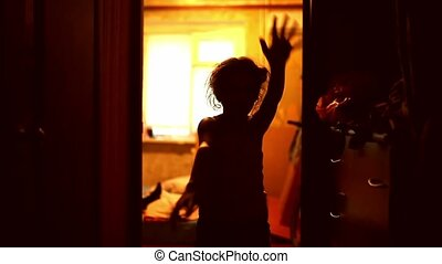 girl teen in zombie is orange silhouette stretched indoor...