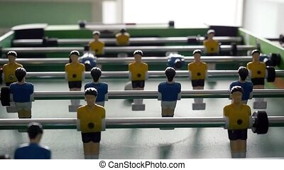 Table football game with yellow and blue players in slowmotion  on blurred background