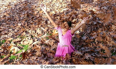 Girl Has Fun In Crisp Autumn Leaves - A cute little 9 year...