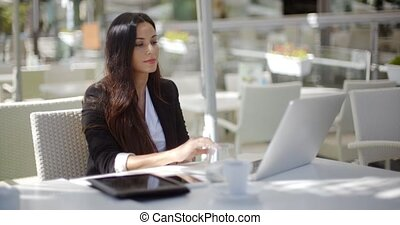 Businesswoman working at an open-air table - Attractive...