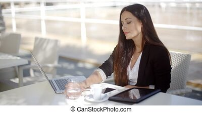 Businesswoman enjoying coffee at a restaurant as she sits at...