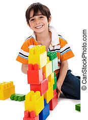 Young boy playing with building blocks on white background