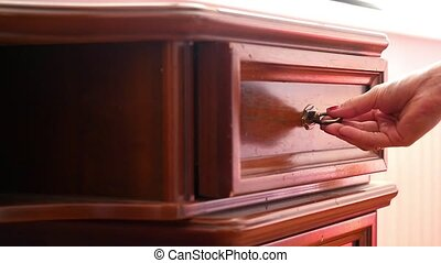 Women hand open old wooden  antique chest of drawers  with metal handles in slowmotion and takes mobile phone