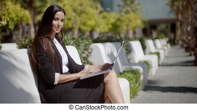 Young woman working on a laptop in the park
