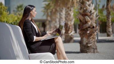 Businesswoman sitting working in an urban park - Attractive...