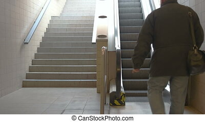 Train Station Escalators - Senior man steps on the escalator