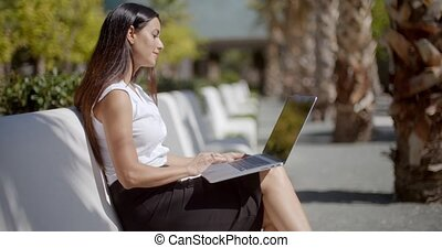 Attractive woman sitting on a bench with a laptop -...