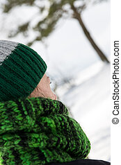 young woman from behind with a green scarf and a wool cap -...