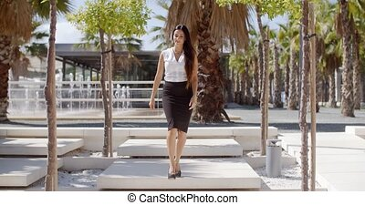 Elegant young woman walking through a park - Elegant young...
