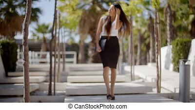Young businesswoman walking through a park - Young...