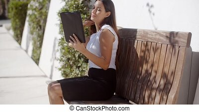 Smiling young woman using her tablet outdoors a she sits on...