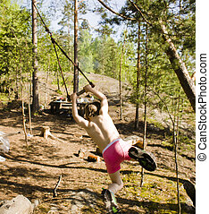 little cute boy flying on bungee among trees at summer...