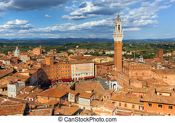 Siena, Italy rooftop city panorama. Mangia Tower, Italian...