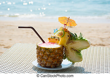 Pineapple cocktail with beautiful sand and sea in background