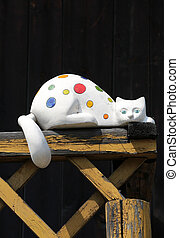 Colorful porcelain cat on wooden balcony