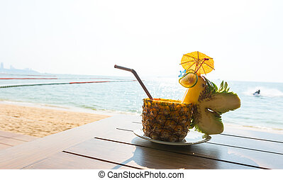Pineapple cocktail with beautiful sea in background