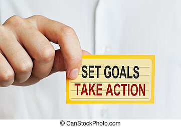 Set Goals, Take Action. Card in male hand