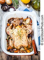 whole baked chicken with vegetables and thyme on wooden...