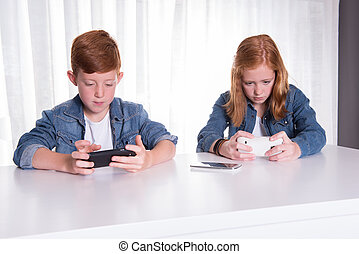 two redhaired kids are playing with their smartphones