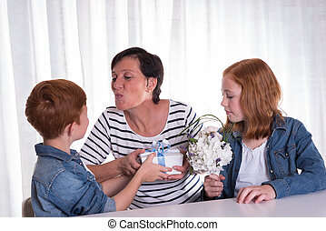 two redhaired kids giving a present to their mother