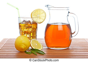 Ice tea pitcher and tumbler with lemon and icecubes on...