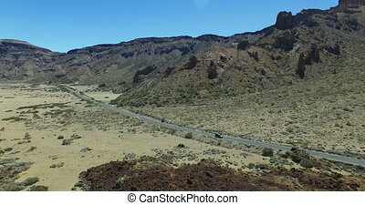 Aerial flight above road through lunar landscape in Teide...