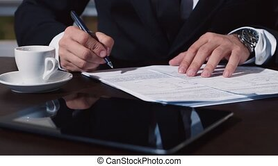 Man's hand in a business suit signs documents