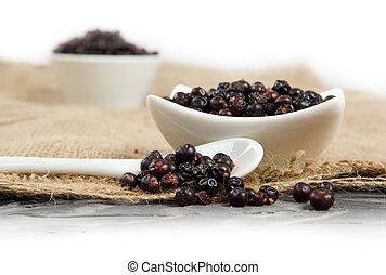 Juniper - Photo of bowls full of juniper spice on burlap...