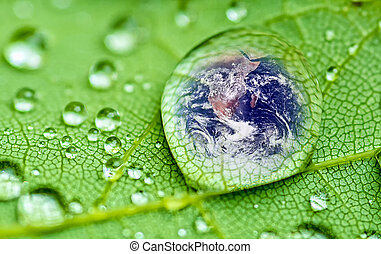Raindrop - planet earth inside a raindrop closeup on a green...