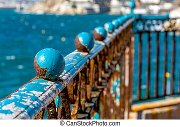 old guardrail - rusty blue guardrail on the sea front, in...