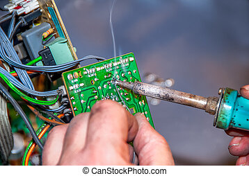 soldering - technician making  a repair with solder