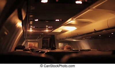 Air Jet airplane interior view at night. Woman passenger...