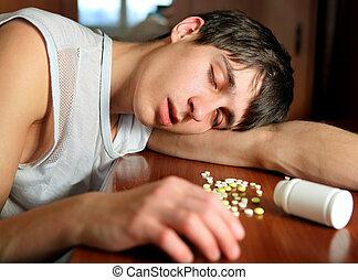 Man sleep on the Table - Young Man sleep near the Pills on...