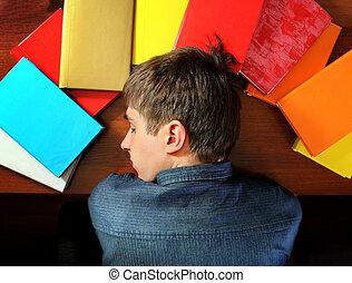 Young Man sleep on the Books - Tired Young Man sleep on the...