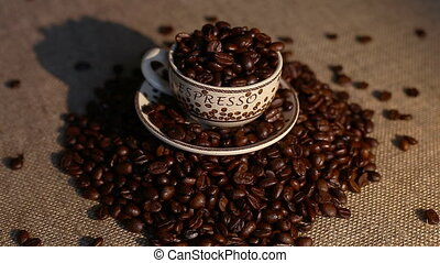 A cup with coffee bean as background - A cup of cappuccino...