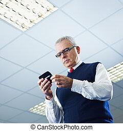mature businessman reading e-mails on cellphone - portrait...