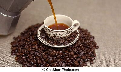 Pouring a cup of coffee with coffee beans - pour a cup of...