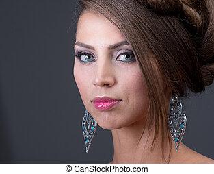Woman wearing shiny blue earring - Woman wearing shiny...