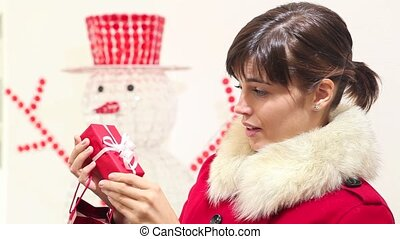 Christmas woman opens bag with gift and smiles, with snowman...