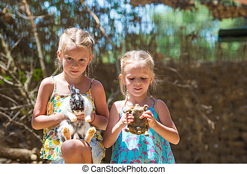 Little adorable girl with a land tortoise and cute rabbit at...