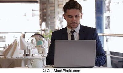 Man using laptop at lunchtime