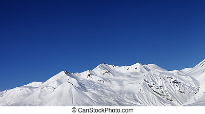 Panoramic view on snowy mountains at sun day. Caucasus...