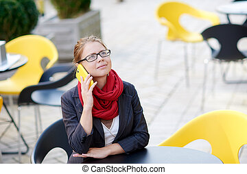 Business woman sitting at a table in a cafe on the phone.