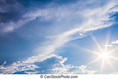 natural lens flare and radiating rays in a blue sky with...
