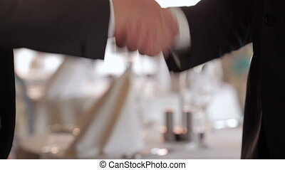 The men shake hands - Business lunch in a restaurant, cafe,...
