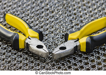 Knitting Chainmail - A pair of pliers on chainmail