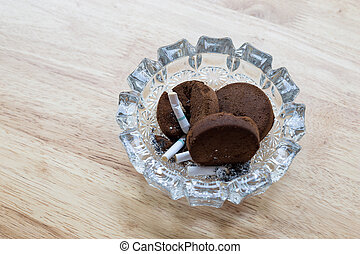 Cigarettes butt in ashtray with reused for grind coffee...
