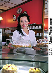 owner of a small business cake store cafe showing her tasty...