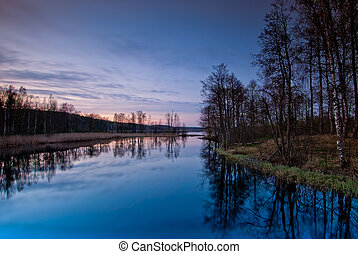 beautiful landscape at sunset. Bare trees around calm lake